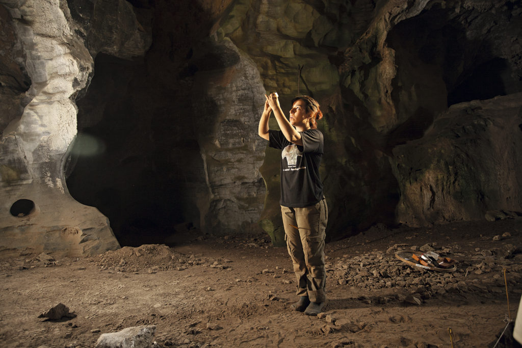 Pesquisadora Me. Daniela Ortega observando um artefato - Lapa do Santo